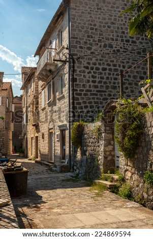Beautiful narrow street of ancient city Perast, Montenegro - stock photo