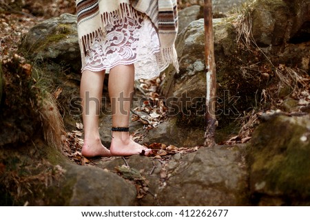 beautiful native indian american woman legs with pikestaff walking on background of woods