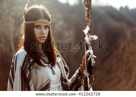 beautiful native indian american woman with warrior shaman make up looking and holding rod - stock photo