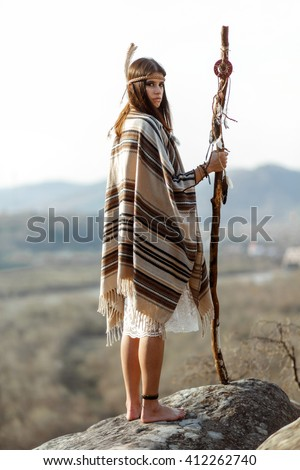 beautiful native indian american woman with warrior shaman make up standing on rocks on background of woods and river - stock photo