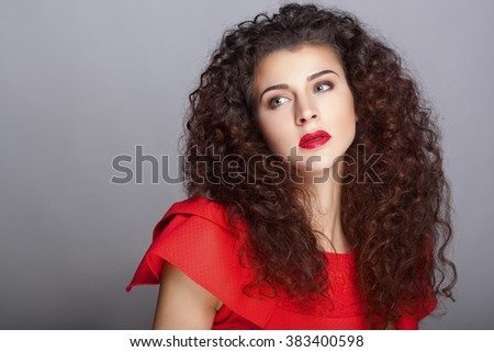 Beautiful natural curly brunette hair, portrait of an young girl with red lips