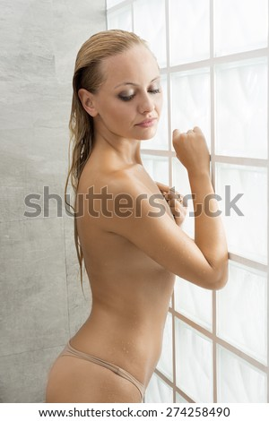 Beautiful, natural, fresh, healthy female with blonde hair and natural make up is standing in the shower, her body is wet, she is looking down. - stock photo