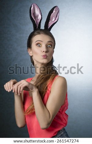 Beautiful, natural, gorgeous, blonde woman with funny, fluffy rabbit ears on the head. She is posing like cute, little rabbit. - stock photo
