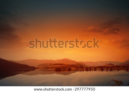 Beautiful natural landscape of mountain lake and field - stock photo