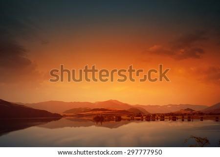 Beautiful natural landscape of mountain lake and field - stock photo