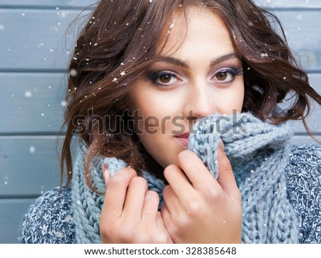 Beautiful natural looking young smiling brunette woman, wearing knitted scarf, covered with snow flakes. Snowing winter beauty concept - stock photo