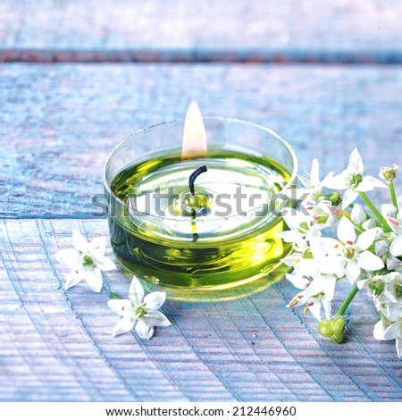 Beautiful natural organic spa background with a spray of delicate white flowers alongside a burning green aromatherapy candle on a blue background in a wellness and pampering concept - stock photo