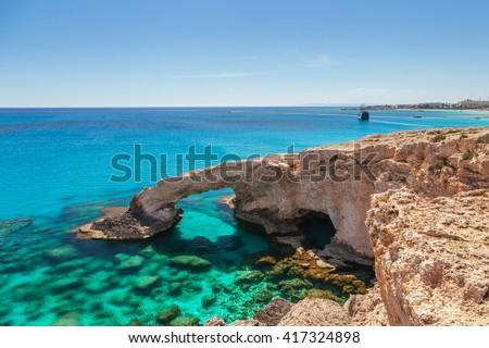 Beautiful natural rock arch near of Ayia Napa, Cavo Greco and Protaras on Cyprus island, Mediterranean Sea. Legendary bridge lovers. Amazing blue green sea and sunny day. - stock photo