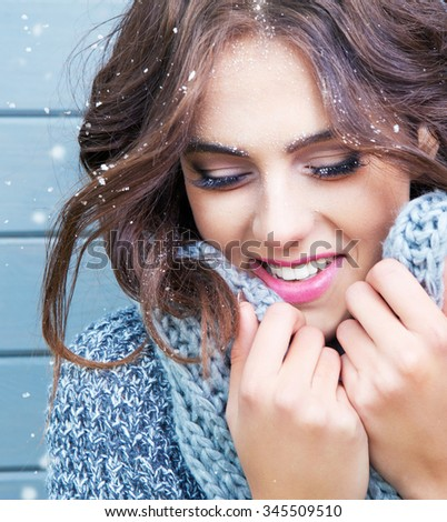 Beautiful natural young brunette smiling woman with eyes closed, wearing knitted scarf, covered with snow flakes. Snowing winter beauty concept - stock photo
