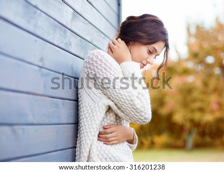Beautiful natural young brunette woman wearing knitted sweater by the house. Fall and winter fashion concept. - stock photo