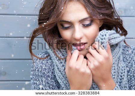 Beautiful natural young  brunette woman with eyes closed, wearing knitted scarf, covered with snow flakes. Snowing winter beauty concept. - stock photo
