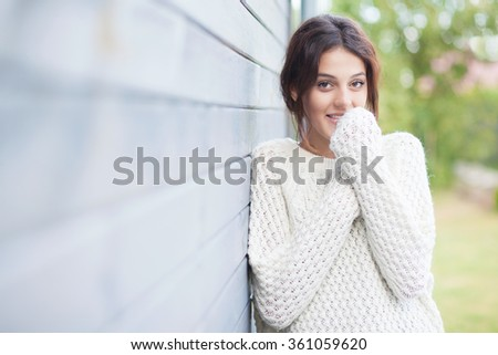 Beautiful natural young smiling shy brunette woman wearing knitted sweater by the house. Fall and winter fashion concept. - stock photo