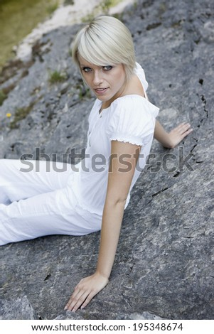 Beautiful natural young woman relaxing reclining back against a granite rock looking up at the camera with a serious expression as she enjoys a day in nature - stock photo