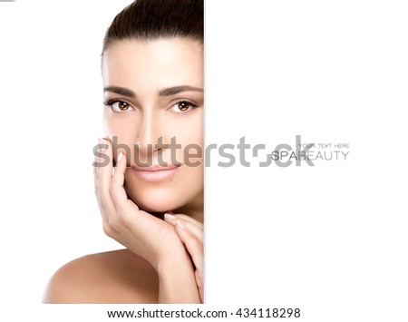 Beautiful natural young woman with a smooth unblemished complexion, hands raised gracefully to her cheek  looking at camera with a friendly expression in a beauty, skincare and spa concept - stock photo