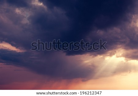 Beautiful nature background. Fantastic colorful sunset and dark ominous clouds. Beauty world.