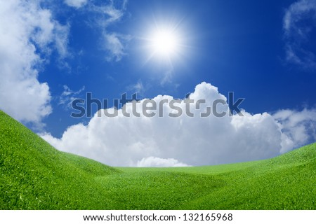 Beautiful nature background - green grass field, bright sun, blue sky, white clouds - heaven on earth