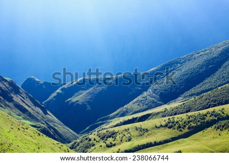 Beautiful nature background - hills, mountains with green grass and trees, bright sunlight from above - stock photo