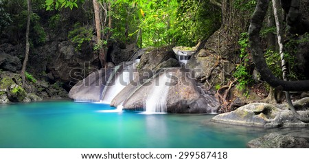 Beautiful nature background. Waterfall flows through tropical rainforest and falls into natural pond - stock photo