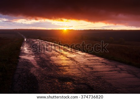 Beautiful nature landscape. Wet asphalt road after rain at sunset - stock photo