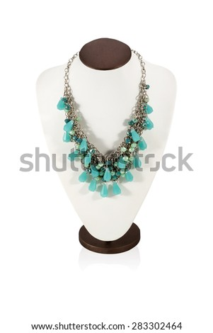 Beautiful necklace of turquoise stones on the metal chain on the bust for display isolated on a white background - stock photo