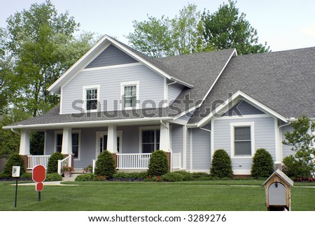 Beautiful new country style wood home featuring a large front porch and nice landscaping. - stock photo