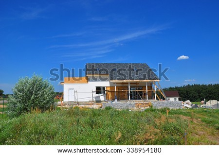 Beautiful New Cozy House Building Construction Exterior. Cozy house with Dormers, Skylights, Ventilation, Gutter, Drainage, Plastering and Using Color.  Outdoor. - stock photo