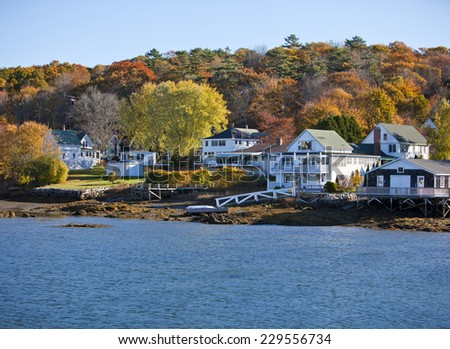 Beautiful New England colonial style homes on the water in fall - stock photo
