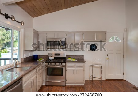 Beautiful New Kitchen in mid century home with, Sink, Cabinets, Wooden Floor  in New Home - stock photo