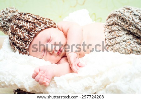 beautiful newborn baby boy sleeping in knitted cap close-up - stock photo