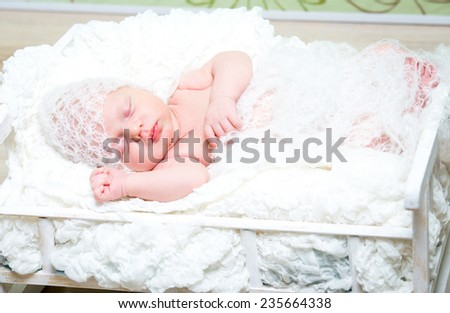 beautiful newborn baby boy sleeps in a small bed in white knitted cap - stock photo