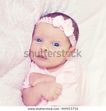 Beautiful newborn baby girl with pink bow and blue eyes closeup