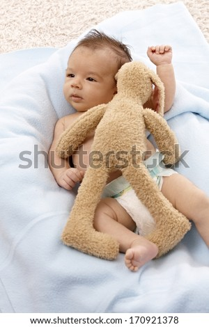 Beautiful newborn baby lying naked with plush bunny. - stock photo