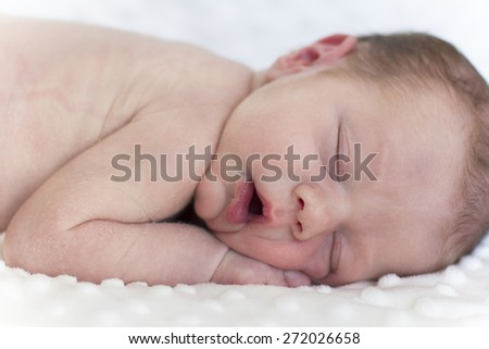 Beautiful newborn baby lying on a blanket and sleeping peacefully