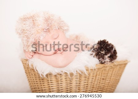 Beautiful newborn baby sleeping in a basket - stock photo