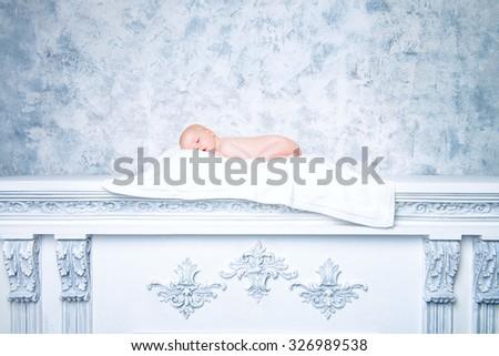 Beautiful newborn baby sleeping peacefully on a white fireplace. Art, vintage style.  - stock photo