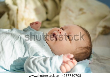 Beautiful newborn baby smiling and laughing. Soft focus - stock photo