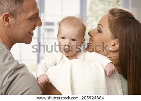 Beautiful newborn baby sticking tongue, parents smiling. - stock photo