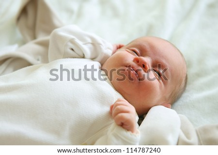 Beautiful newborn baby stretching in his bed - stock photo