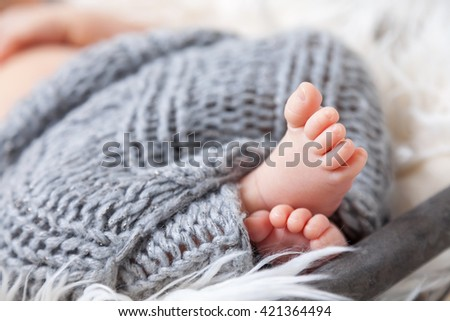 Beautiful newborn baby toes inside a wicker basket - stock photo
