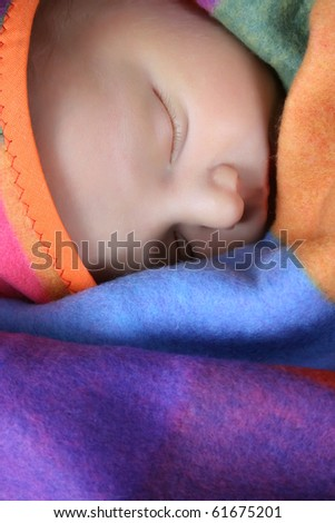 Beautiful newborn boy wrapped in a colorful blanket - stock photo