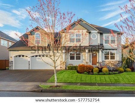 Beautiful, Newly Built Luxury Home Exterior with Lush Green Grass, Driveway, Garage, and Trees, in Suburban Neighborhood