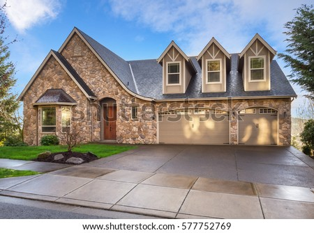 beautiful newly built luxury home exterior with stone facade and three car garage and - Luxury Homes Exterior Brick