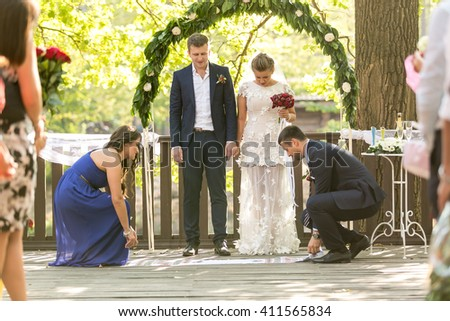 Beautiful newly married couple having traditional unity rite during wedding ceremony - stock photo