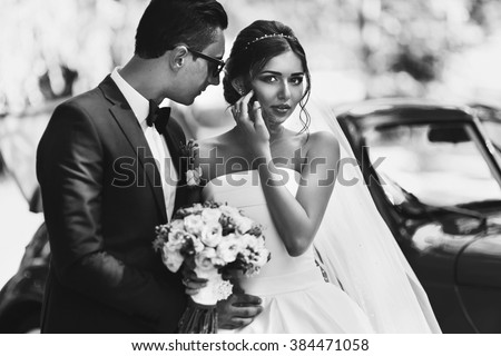 Beautiful newlywed couple posing near retro wedding car b&w