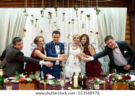 beautiful newlyweds with their friends standing at the table