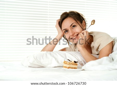 Beautiful nice girl lying on a bed with a cake on a light background - stock photo