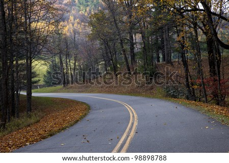 Beautiful, nicely paved winding road lined with colorful autumn leaves - stock photo