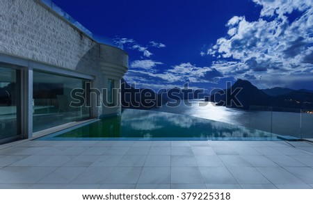 beautiful night scene from a modern house with infinity pool - stock photo