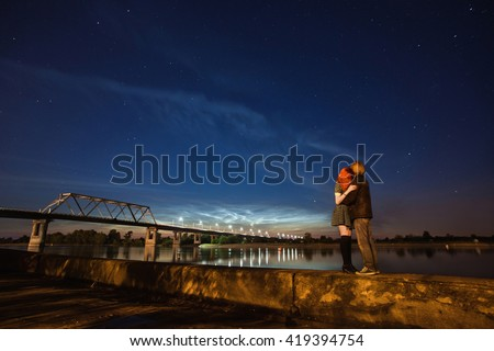 beautiful night scenery, the stars in the night sky, a couple on a background of the night sky, red-haired girl and a guy, noctilucent clouds on the horizon, surface of water, bridge over the river - stock photo