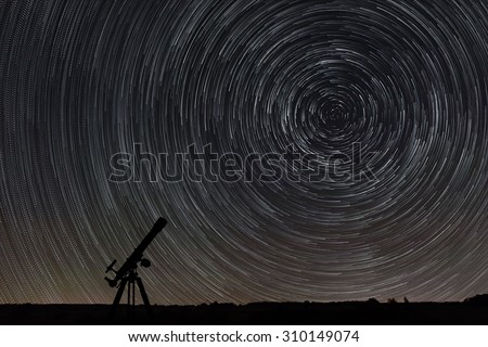 Beautiful night sky, Star trails over filed and astronomical telescope - stock photo